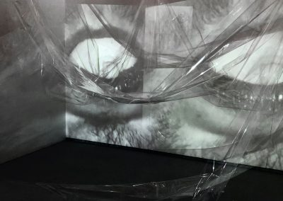 Black and white projected image of an open mouth in which teeth are biting down on a breast made from soft icing, with clear cellophane wrinkled in space across the projected image.