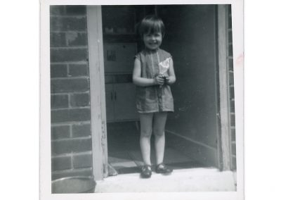 Black and white family photograph showing a little girl of about six years old standing in an open doorway. She is wearing a short summer dress and is holding what appears to be a cone of rolled up paper. She is smiling.