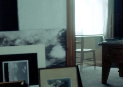 A photograph of many layers. To the left of the frame are some framed pictures stacked against a wall. Some show landscapes and clouds, another is a framed family wedding photograph c.1920. To the left of the frame is a mirror in which is reflected a table and a window with an empty child's chair that is a ghost image from a double exposure.