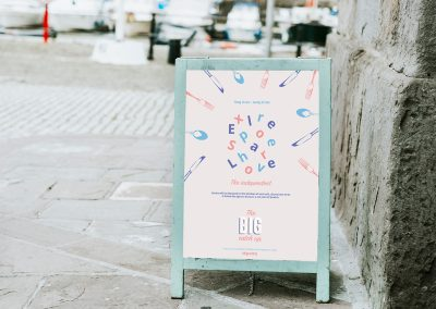 A mock-up displaying an advertising poster for the Big Catch Up event presented on an easel.