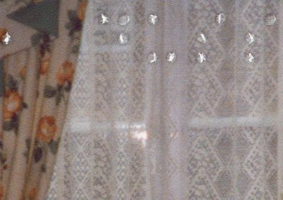 Cropped as a rectangle, the image focuses around a set of curtains on a window going across the majority of the canvas. The curtains feature orange and green flowers on a cream background, tied up at each end of the window, with white lace curtains covering the glass of the window. Only the top half of the window is visible. The braille goes across the piece, and says 'Christmas, Dussindale, 1990s'.