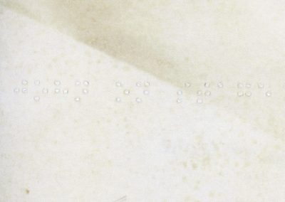 The image features the back of a physical photograph. The paper is cream, with some visible stains and creases. The brand 'Agfa-Brovira' is printed twice on the paper, and show at the top and bottom left. The braille goes across the centre of the piece, and says 'John On Stage'.