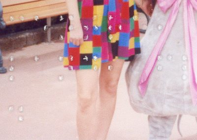 Cropped as a rectangle, the image has been taken at Disneyland. It features a woman standing with someone in costume to have their picture taken, but they are only visible from the waist to the bottom of their legs. The woman is standing in front of a bench, and is wearing a bright, multi-coloured, checked dress, while the other person is dressed in a light grey mouse costume with a pink bow. The braille goes across the image, and reads 'Epcot Centre, Disneyland, Florida, Oct 92.'