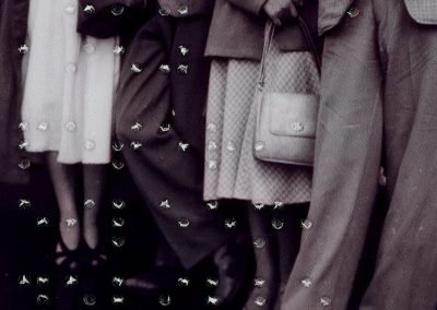 Cropped as a square, the black and white image features four people shown from the waist down. The woman on the left is wearing a white skirt and black heels with a black handbag. The man next to him is wearing black shoes, trousers, and jacket, and is standing with his legs crossed. The woman next to him is wearing a white checked skirt, with heels, a white handbag, and a grey jacket. The man next to her is wearing light grey trousers and a checked-patterned jacket. His shoes aren't visible. The braille goes across the image and reads 'July 23rd 1950 Peter, Eileen, Neville'.