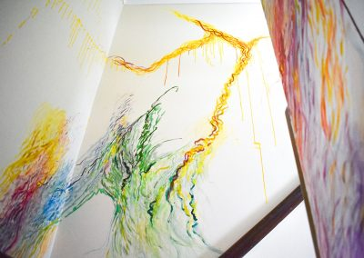 Photograph of a stairwell from the bottom of the stairs. An abstract painting is upon the magnolia walls. The colours used are mostly greens, vibrant pinks, purples and yellow.