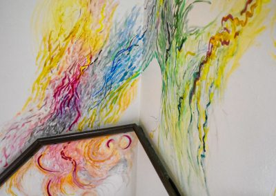 Photograp of an abstract painting sited in a stairwell. Lines made from bright colours fill the space, flowing upwards into the roof of the stairwell. Short and long strokes made form acrylic and silk paint cover the magnolia walls. Text is visible within the paint, but is unreadable.