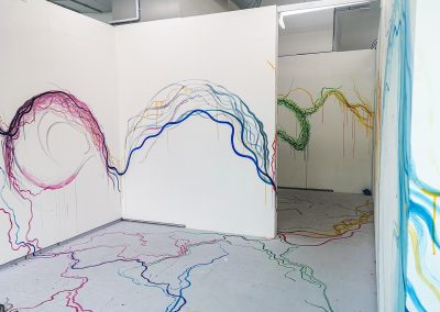 Photograph of immersive abstract painting in studio space. Three walls are visible, two to the left and one to the right making a corridor. The paint on the left is mainly bright blue and grey long lines, moving across the white walls. On the right wall is a large watercolour blue section, trailing into a warmer yellow and red, followed by a deeper green. The colour is trickling onto the floor, making lines moving from one wall to the next.