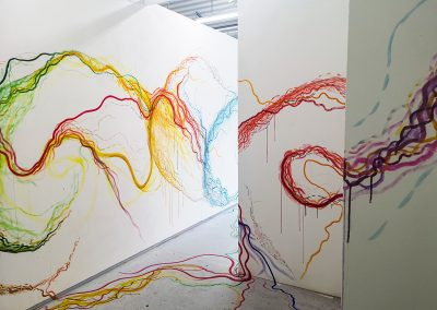 Photograph of studio space, two walls on the right and one on the left depicted here. Each wall has painted lines and brush strokes on them of purple, red, blue, yellow and green, all merging into one-another. The marks trail onto the floor, making the space an immersive experience.