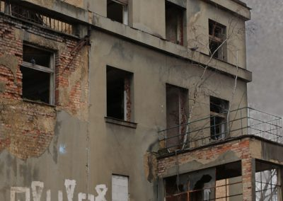 """A photograph of abandoned building in Prague photomontaged with low opacity photograph of blue sprayed text """"Bring abandoned buildings back to life"""" on the rust background from manifesto."""