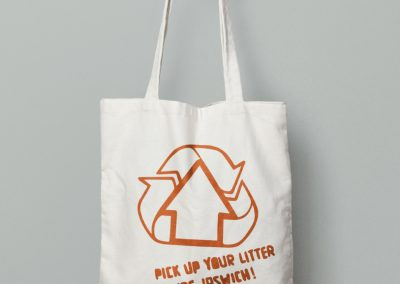 A tote bag featuring a variant on the recycle logo, modified to include a house in the centre of the three interlinked arrows. Below this sits the caption 'pick up your literature, Ipswich!' in handmade lettering.