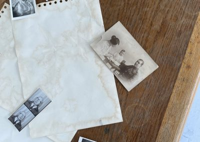 Birds-eye view of black and white, and sepia tone photographs which are scattered over the top of the desk. Underneath them are a few pages of coffee-stained paper. The photographs on the table are: two images of young children, one that shows two images of the same man in the style of a photobooth roll of images, one of a mother and father sat with their baby on a table, and one of