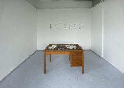 Wide shot of the desk installation with 7 cello-tape transfers hanging on the wall behind the desk. The top of the wooden desk is scattered with black and white photographs and coffee-stained paper.