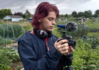 Frankie holds a Canon 800D with a microphone and headphones attached, standing in front of trees and crops.