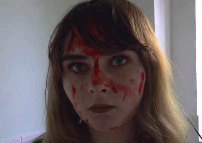 A close up shot of The Girl with brunette hair and blue eyes is staring at the camera. Her face is covered in red blood (but not her own). Behind the girl is a white wall. The girl appears angry.