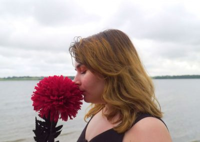 A close-up side shot of the Girl with brunette hair is sniffing a giant red flower. Behind the girl can be seen the grey sea again which is taking up 50% of the back ground. The other 50% is taken up of the grey sky above. Behind the girl at her nose level can be seen a thin strip of land in the distance separating the sea from the sky.