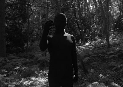 A black and white medium shot of a Man in a black morph suit (known as The Shadowman) about to click his fingers. Behind the Shadowman in black and white can be seen forest background with multiple trees and a grassy floor.