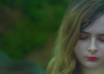 A close-up shot of the Girl with brunette hair is facing the camera, but with her eyes closed. The girl is in a dream like state. Behind the girl can be see multiple bright green bushes blured out of focus.
