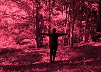 A red tinted very long shot of The Shadow man in the middle of frame extending his arms out like a bird. Behind The Shadowman are a variety of different tall trees. All of the image is in red.